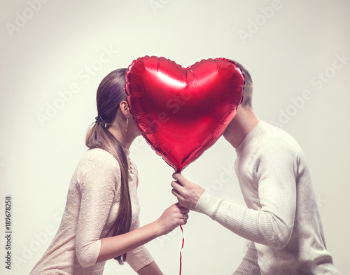 Leinwandbild Motiv Valentine's day. Happy joyful couple holding heart shaped air balloon and kissing. Love