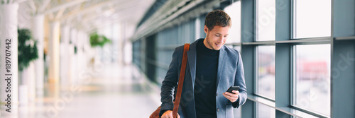 Foto Murales Man holding phone - young businessman using smartphone in airport. Casual urban professional business man texting cellphone happy inside office banner panorama with copy space on background.
