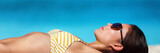 Beach vacation woman sun tanning bikini wearing sunglasses for solar protection eye care. Young girl lying down sunbathing relaxing. Skincare UV sun shade banner panorama. - 189707677