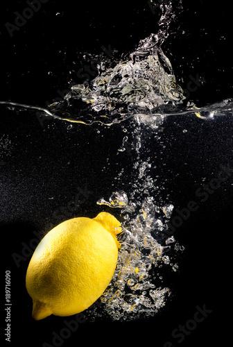 zolta-cytryna-w-wodzie-na-czarnym-tle