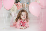 A little girl of 6 years with long curly hair,a beautiful smile, sits alone in a large bright room with lots of pink balloons in the shape of a heart. Valentine's Day and party celebration. - 189720845