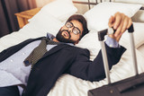 Tired Businessman resting in hotel room - 189721258