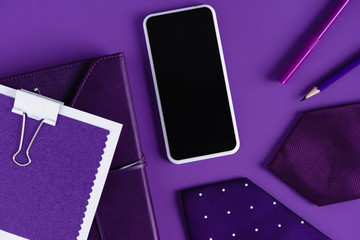 top view of stylish workspace in purple color shades with smartpohone and supplies