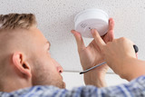 Person's Hand Installing Smoke Detector On Ceiling - 189731494