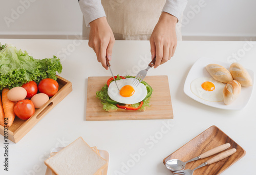 Hands of man prepare breakfast with sandwich with poached eggs