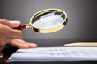 Judge Looking At Document With Magnifying Glass