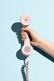 Woman's hand holding a pastel telephone