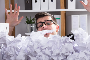 Close-up Of Businessman Behind Heap Of Crumpled Paper