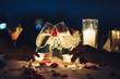 Leinwandbild Motiv Romantic candlelight dinner table setup. Man & Woman hold glass of Champaign.