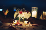 Romantic candlelight dinner table setup. Man & Woman hold glass of Champaign. - 189775020