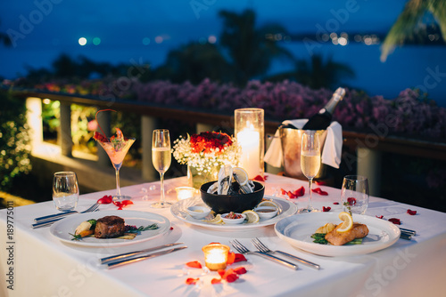 Romantic candlelight dinner table setup for Valentine's day with Champaign & wine glasses and special dishes - 189775011