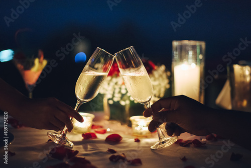Romantic candlelight dinner table setup. Man & Woman hold glass of Champaign. © 9mot