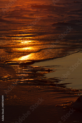 Foto op Canvas Rood paars flares of the sun on the ice on the river