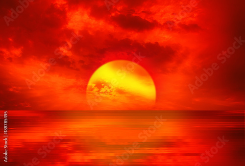Fotobehang Rood An abstract landscape with sunrise over a slightly wavy surface of the sea