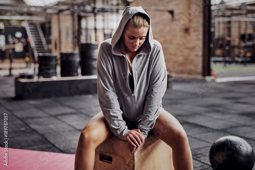 Plexiglas Fitness Young woman in sportswear sitting on a box before exercising