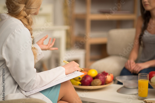 Female nutritionist giving consultation to patient. Making diet plan.