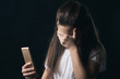 young sad vulnerable girl using mobile phone scared and desperate suffering online abuse cyberbullying being stalked