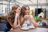 smiling young women drinking coffee at street cafe - 189794612