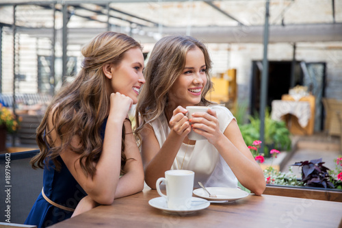 smiling young women drinking coffee at street cafe