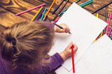 Little girl draws with pencils on a wooden table - 189799808