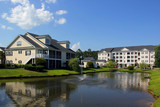 Southern modern architecture and vacation rentals background. Myrtle Beach suburb neighborhood morning view with buildings around the pond with sprinkling fountain. South Carolina, USA. - 189804671