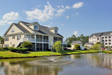 Southern modern architecture and vacation rentals background.. Myrtle Beach suburb neighborhood morning view with buildings around the pond with sprinkling fountain. South Carolina, USA. - 189804696