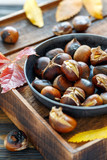 Roasted chestnuts in a cast iron skillet. - 189825839