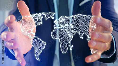 Fototapeta Businessman holding a Hand drawn world map on a futuristic interface
