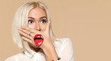 Young woman with blonde hair and painted red lips on her hand. Portrait of fashionable female person on beige background. Emotion of surprise and fright. Concept of tomfoolery and fun. - 189848626