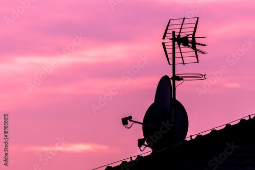 Foto op Canvas Candy roze Silhouette of roof with satellite and antenna on nice vibrant violet and pink sky