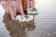 Girls in light dresses travel on a raft with a sail. The girls launch wreaths of white flowers.