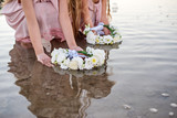 Girls in light dresses travel on a raft with a sail. The girls launch wreaths of white flowers. - 189860000