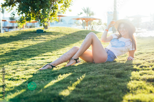 Deurstickers Zwavel geel Young beauty woman lying on the grass on summer vocation sunshine near sea