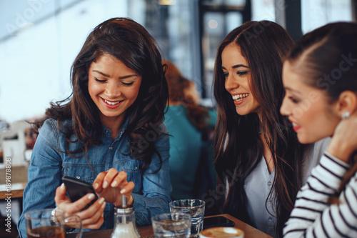 Sticker Three young women having fun at a coffee shop