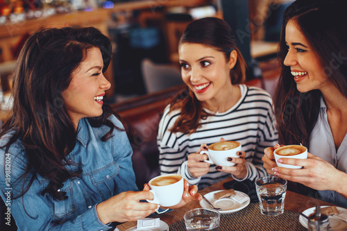 Three young women enjoy coffee at a coffee shop - 189882024