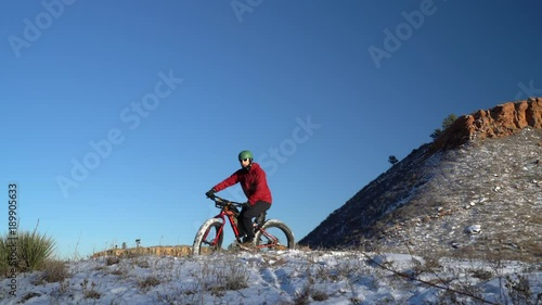 Male cyclist riding a fat mountain bike on a snowy trail in Horsetooth Mountain Park near Fort Collins, Colorado