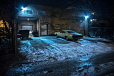 Vintage muscle car in a dark Chicago city urban alley on a winter night.