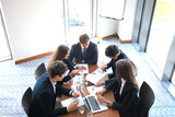 Business meeting in an office, the businesspeople are discussing a document. - 189925087
