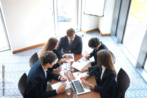Business meeting in an office, the businesspeople are discussing a document.