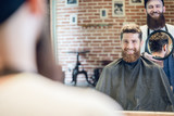 Over the shoulder view of a handsome young man smiling, while looking at his new trendy haircut in the mirror held by his experienced barber in a cool hair salon