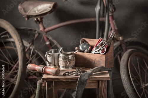 Plexiglas Fiets Vintage bicycle repair workshop with tools, wheels and tube
