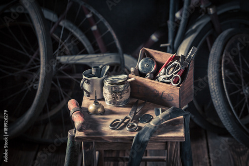 Foto op Canvas Fiets Old bicycle repair workshop with tools, wheels and tube