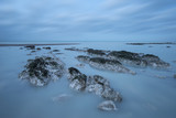Stunning long exposure landscape image of low tide beach with rocks at sunrise - 189930803