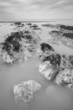Stunning black and white long exposure landscape image of low tide beach with rocks at sunrise - 189930898
