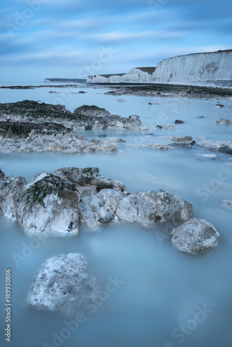 Fotobehang Blauwe jeans Stunning long exposure landscape image of low tide beach with rocks at sunrise