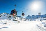 ski lift gondolas against blue sky over slope at ski resort on sunny winter day at Italy Alps - 189931671