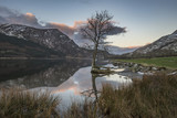 Stunning sunrise landscape image in Winter of Llyn Cwellyn in Snowdonia National Park with snow capped mountains in background - 189932400