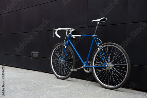 Fotobehang Fiets Vintage blue city bicycle against a black wall