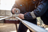 Focus hand view of professional industrial workers in uniform bonding metal pipe with duct tape. - 189942023