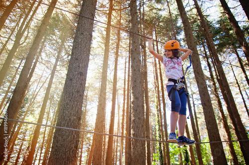 bambina in equilibrio sul percorso del parco avventura